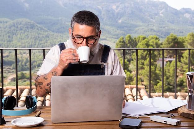 屋外の自宅のテラスでノートパソコンと一緒に座って仕事をしながらコーヒーを飲む大人の男性