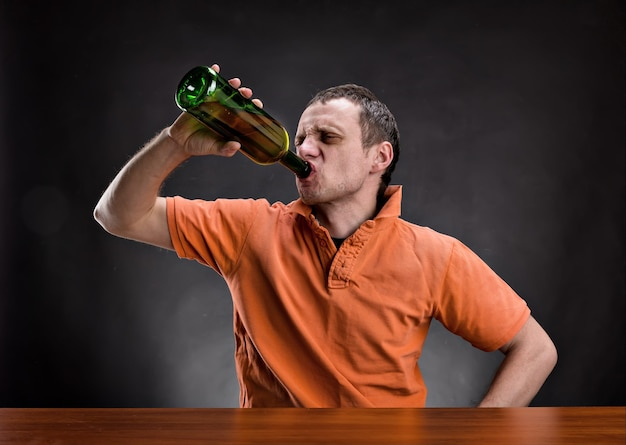 Взрослый мужчина пьет алкоголь над серым