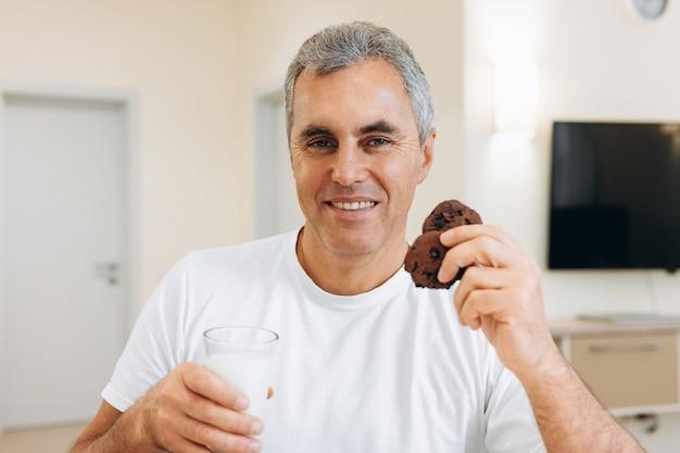 Взрослый мужчина ест печенье и пьет молоко