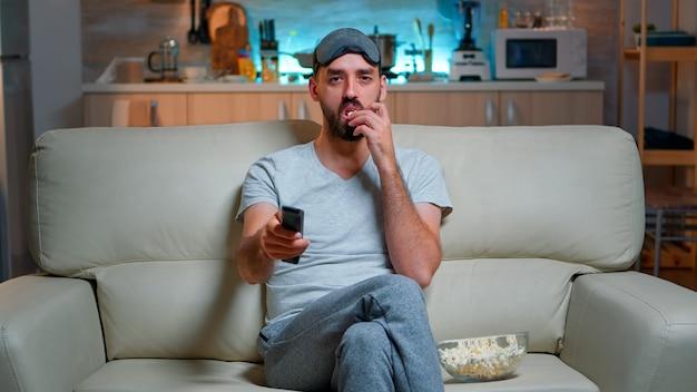 Взрослый мужчина ест попкорн, стоя перед телевизором