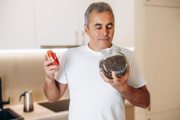 Взрослый мужчина наслаждается запахом кофейных зерен с закрытыми глазами