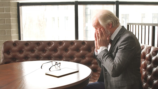 An adult man fashionably dressed rubs tired eyes while sitting at a table
