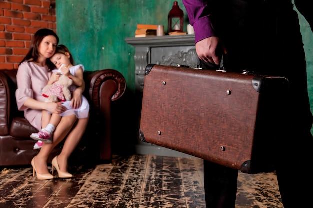 Отец и муж взрослого человека уезжают из семьи с чемоданом. концептуальные проблемы в семье, безотцовщина и материнство-одиночка. грустная мама и дочь на стуле в гостиной присматривают за уходящим папой