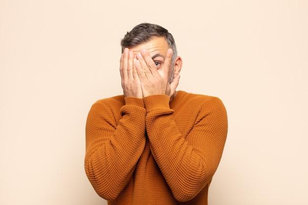 Взрослый мужчина чувствует страх или смущение, подглядывает или шпионит с полузакрытыми руками глазами