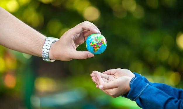 小さな女の子に地球儀を与える大人の男性