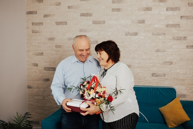 Adult man giving a surprise gift and flowers at her beloved wife on her birthday day.