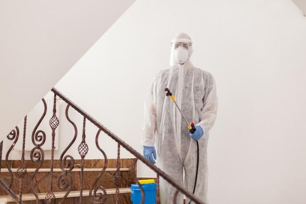 Adult man in hazmat suit spreading antibacterial against coronavirus.