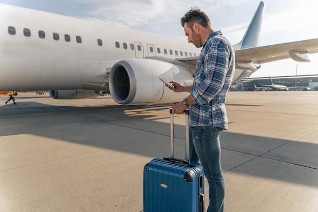 Adult man holding mobile phone near plane
