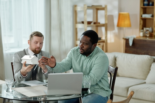 Adult man holding mockup house and advising black man on home loan sitting at table