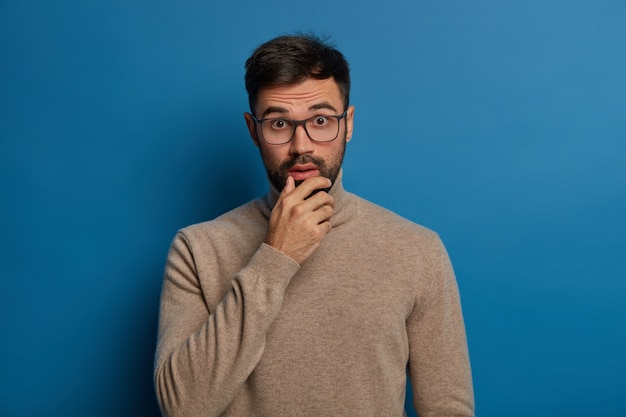 Adult man holds chin, looks with shock at camera, has embarrassed expression, reacts on unexpected news, wears transparent glasses and casual jumper, stands against blue wall.