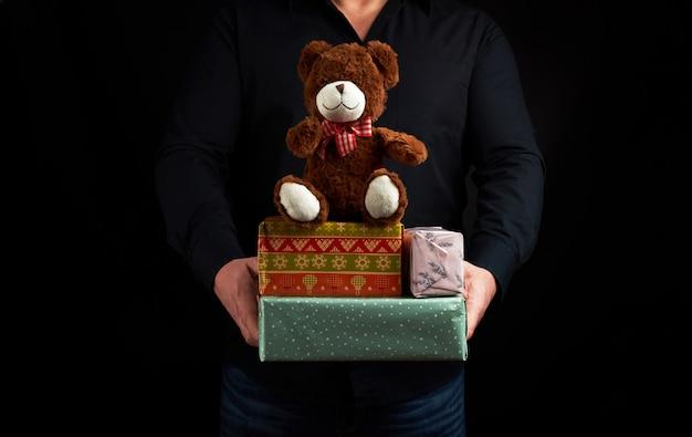 Взрослый мужчина в черной рубашке держит синюю квадратную коробку, перевязанную красной лентой и коричневого плюшевого мишку