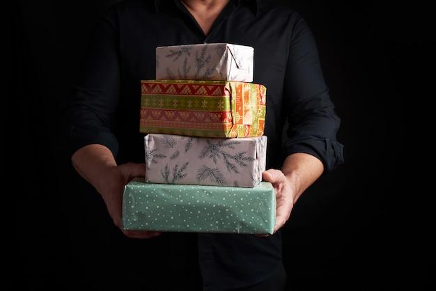 黒いシャツを着た大人の男は、彼の手で紙で包まれた贈り物のスタックを保持しています