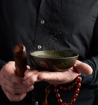 Взрослый мужчина в черной рубашке вращает деревянную палочку вокруг медной тибетской миски с водой. ритуал медитации
