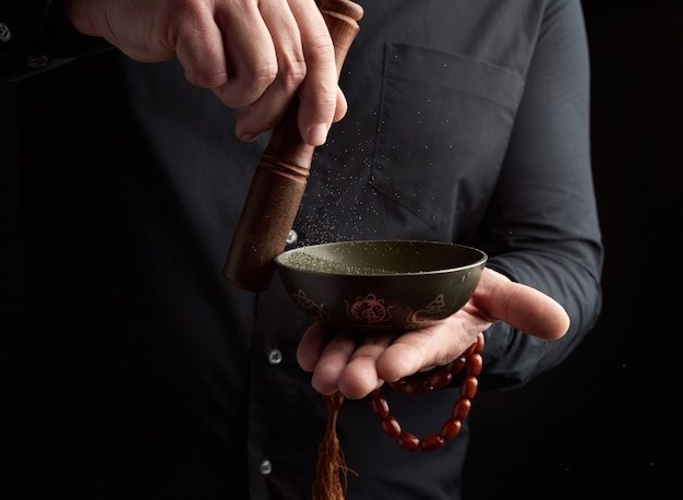 Взрослый мужчина в черной рубашке вращает деревянную палочку вокруг медной тибетской миски. ритуал медитации