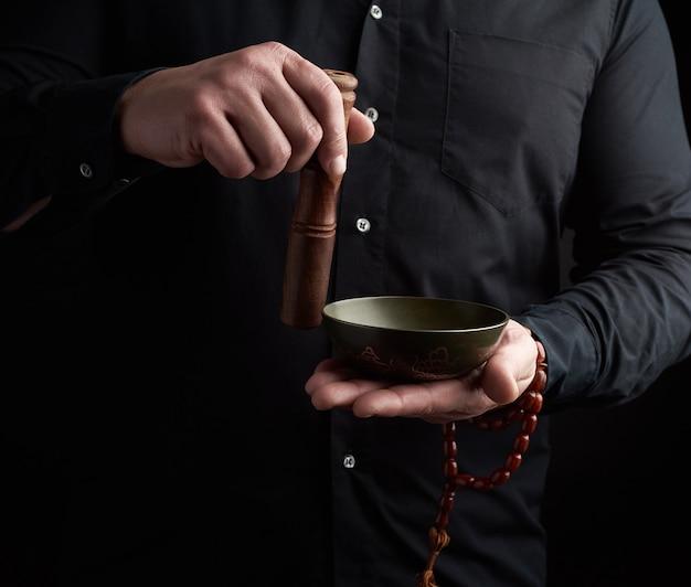 Взрослый мужчина в черной рубашке вращает деревянную палочку вокруг медной тибетской миски