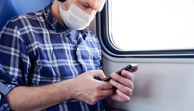 Взрослый мужчина в пригородном поезде в наушниках и медицинской маске с телефоном слушает музыку