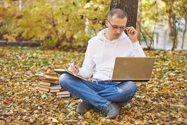Взрослый мужчина в белой толстовке с капюшоном учится в парке на ноутбуке, пишет в блокноте, читает книги и учебники. обучение на открытом воздухе, социальное дистанцирование