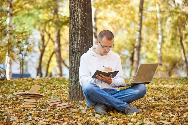 白いパーカーを着た成人男性が、ノートパソコンで公園で勉強し、ノートに書き込み、本や教科書を読んでいます。野外学習、社会的距離