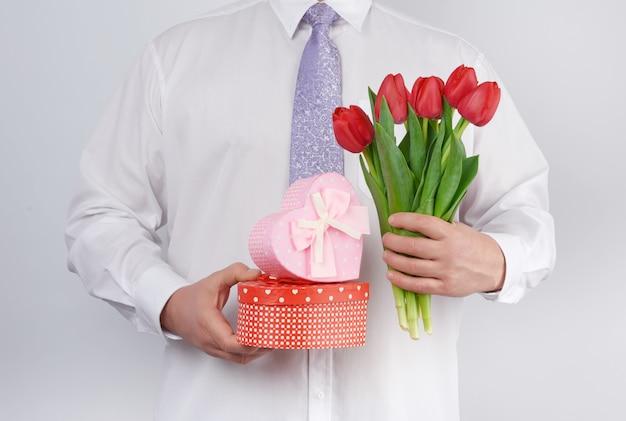 Взрослый мужчина в белой рубашке и сиреневом галстуке держит букет красных тюльпанов с зелеными листьями и подарочной коробкой