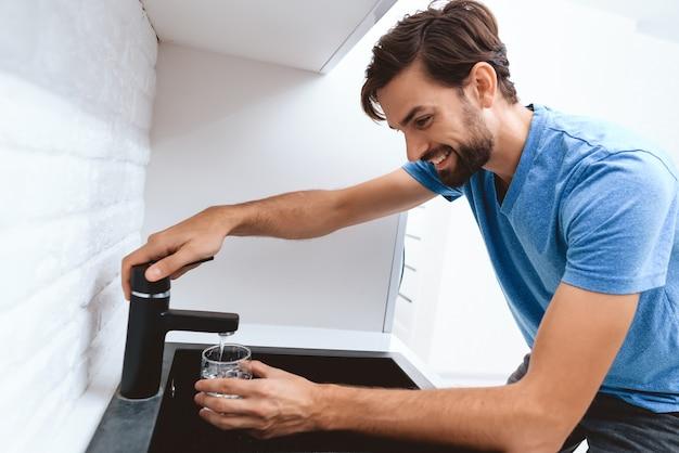 Взрослый мужчина в синей футболке пьет воду из крана.