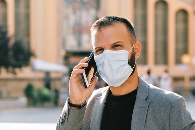 Взрослый мужчина в сером повседневном костюме с маской и социальной дистанцией