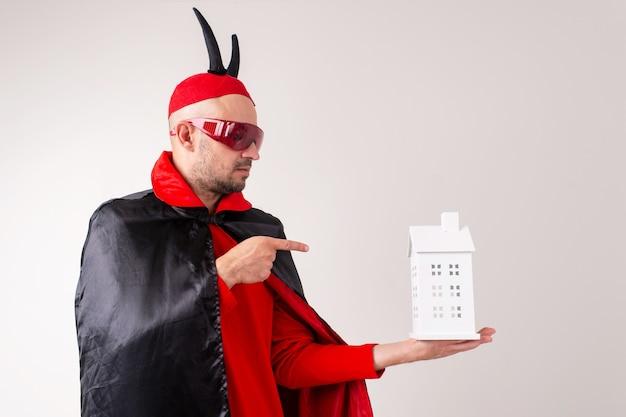 彼の手に装飾的な建物を持つハロウィーンの衣装で大人の男