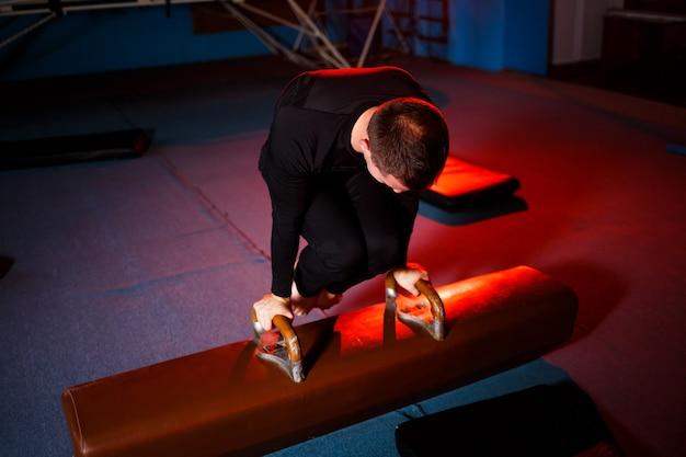 곡예 체육관에서 체조 기구에 운동을 하는 운동복을 입은 성인 남자
