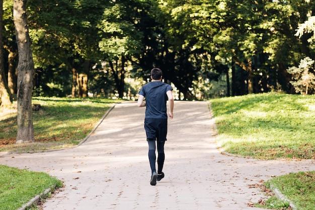早朝に公園でジョギングスポーツウェアの成人男性