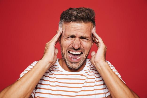 赤で隔離された頭痛のためにこめかみを叫んでこめかみの縞模様のtシャツの大人の男