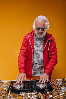 Взрослый мужчина в стильном наряде и синих солнцезащитных очках играет музыку с диджейским контроллером