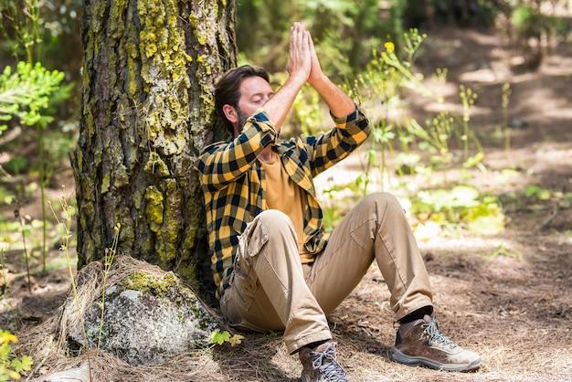 숲 속의 성인 남자는 땅에 앉아 명상을 하고 주변의 야외 자연과 사랑에 빠졌습니다 - 건강한 생활 방식과 행복한 평화로운 사람들의 개념