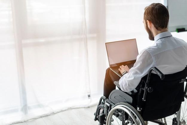 Взрослый мужчина в инвалидной коляске работает на ноутбуке