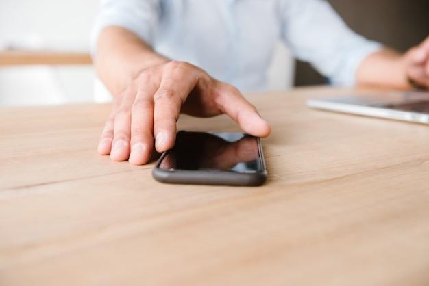 Взрослый мужчина в белой рубашке берет мобильный телефон со стола, сидя и работая в офисе