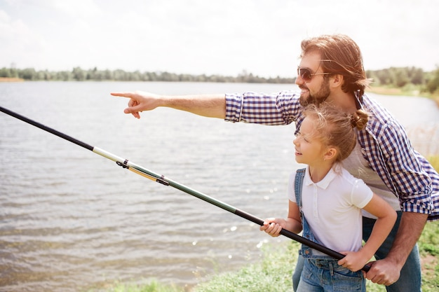 Adult man is pointing forward and showing it to his daughter. he wears glasses. girl is standing with him and holding fish-rod. she is fishing.