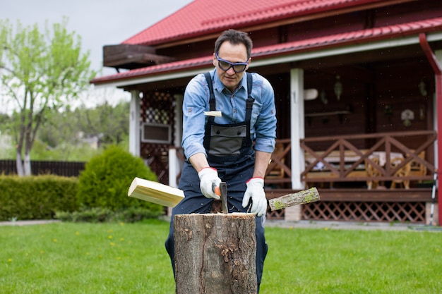 Adult man in jeans shirt and overalls chopping wood with axe in rural.