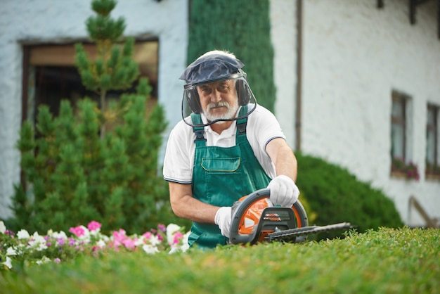 Adult man landscaping bushes with hedge cutter.