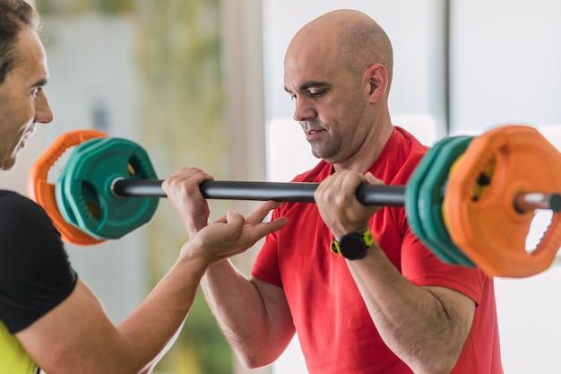 Взрослый мужчина поднимает тяжести с помощью личного тренера в тренажерном зале