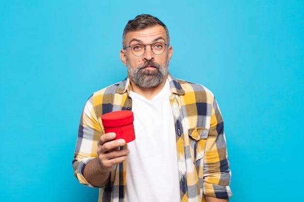 Взрослый мужчина выглядит озадаченным и сбитым с толку, нервно прикусывает губу, не зная ответа на проблему