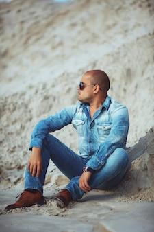 Взрослый человек лежал в джинсовой одежде на песке в бразилии