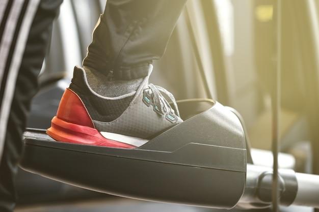 Взрослый человек, делая кардио тренировки упражнения в клубе gym closeup горизонтальное тонирование