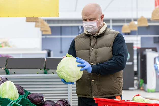 Adult man in a medical mask and gloves picks cabbage in the vegetable department of a supermarket.