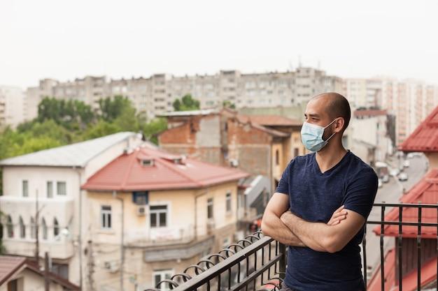 世界的大流行の際にフェイスマスクを着用したバルコニーの成人男性。