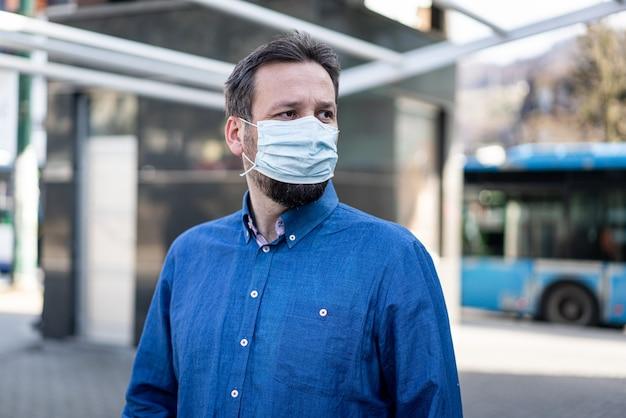 コロナウイルスに対するマスクを持つ街の成人男性