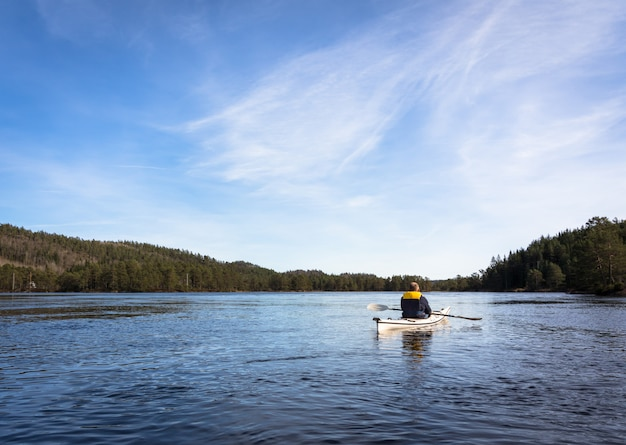 Adult man paddling norwegian river in white kayak in nidelva, norway