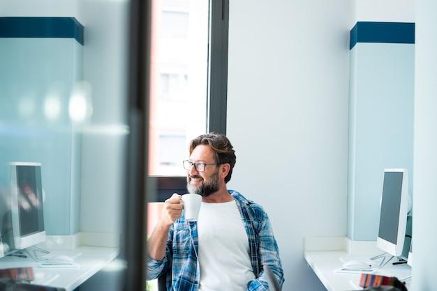 仕事の休憩をしているデスクトップオフィスに座ってコーヒーを飲み、窓の外を見ている成人男性の肖像画-オンラインフリーランスの従業員のライフスタイル活動-成熟した白人の人々とコンピューター