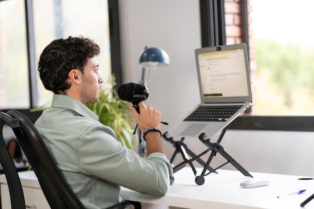 성인 남자가 집에서 팟 캐스트를 녹음하고, 디지털 홈 워크 개념, 젊은 기업가