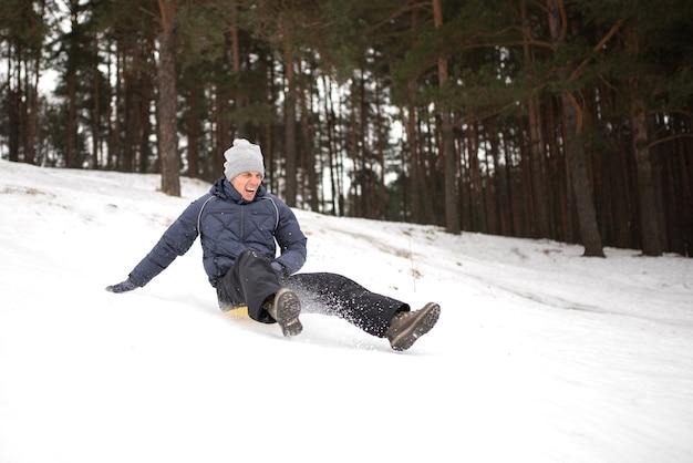 大人の男が急な山からそりの氷に乗る。冬の楽しみ。あらゆる目的のために。