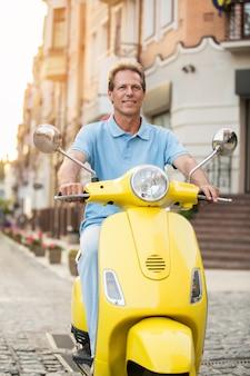 大人の男性が黄色いスクーターに乗る。