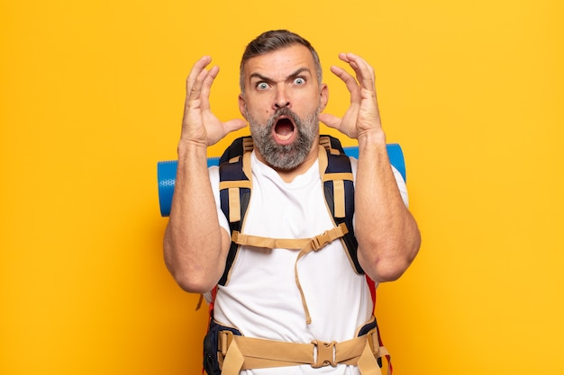 Adult man screaming with hands up in the air, feeling furious, frustrated, stressed and upset