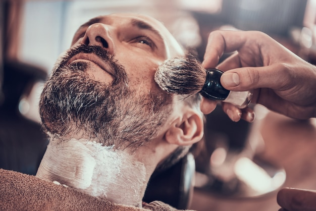 Adult man shave in a stylish barbershop